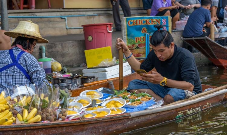 Vendor on cell phone damnoen saduak floating market Bangkok Thailand
