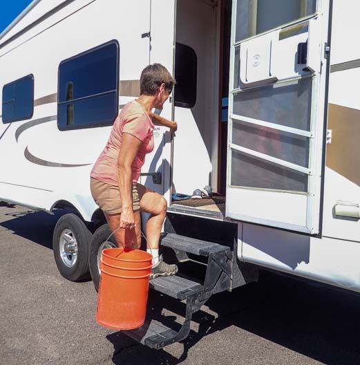 RV dump station tip flush black tank with buckets of water in toilet