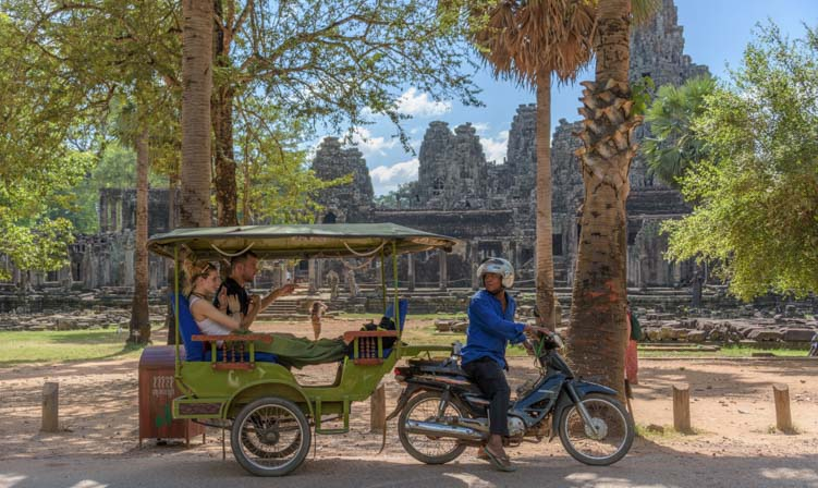 Tuk-tuk driver with passengers at Angkor Wat in SIem Reap Cambodia