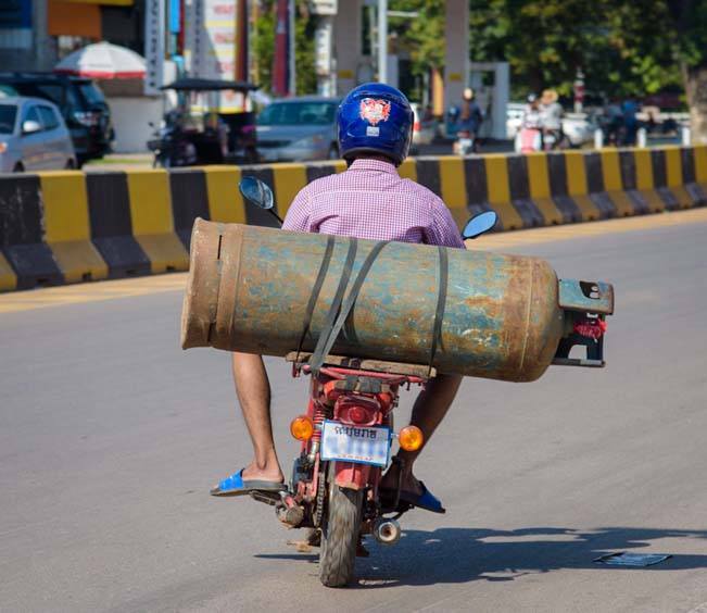 Motorbike carrying a large cannister Siem Reap Angkor Cambodia