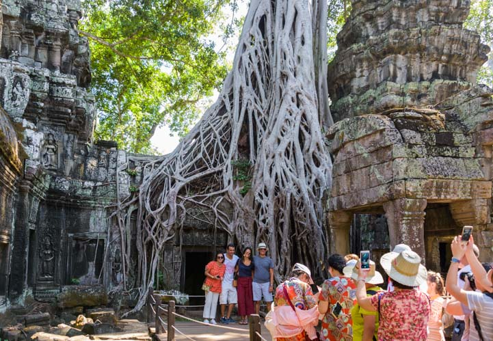 Tourists at jungle temple Ta Prohm Angkor Siem Reap Cambodia