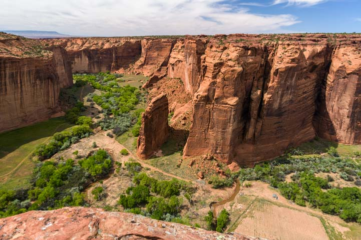 Red rock cliffs and green valley floor Sliding House Overlook Canyon de Chelly National Monument Arizona