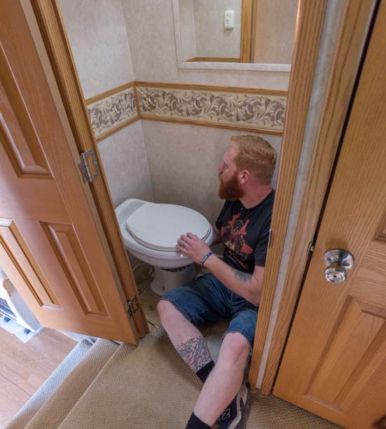 Installing new RV toilet in tiny RV toilet room in fifth wheel trailer