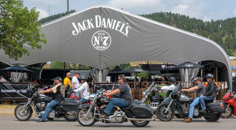 Motorcycles pass Jack Daniels booth Sturgis Motorcycle Rally South Dakota