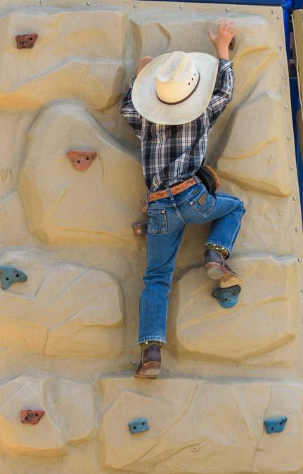 Young cowboy climbs the rock climbing wall Buffalo Wyoming Basque Festival