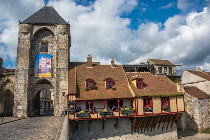 Medieval gate and restaurant on the river Moret sur Loing France-min