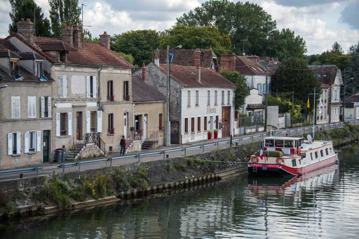 Barge and riverside buildings Moret sur Loing France-min