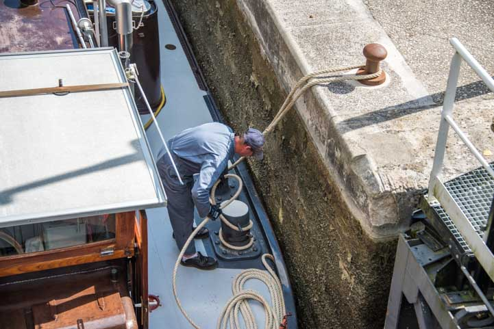 Captain ties up barge at locks Moret sur Loing France-min
