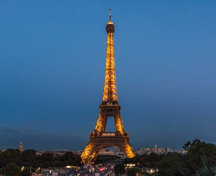 Eiffel Tower lit up at night Paris France-min