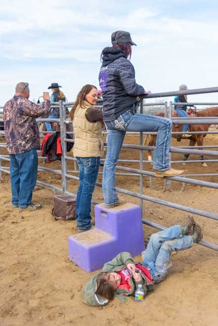 Tired cowgirl lies on the ground at cattle sorting in Arizona ranch-min