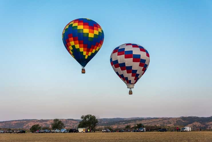 Fall River Balloon Festival balloons fly over landscape-min