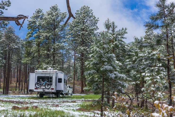 Fifth wheel RV in snow and woods of New Mexico-min