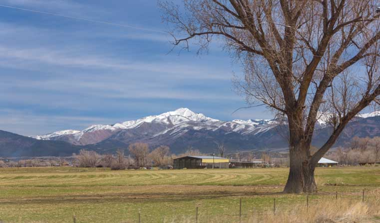 Farm fields and snowcapped mountains near Cedar City Utah-min