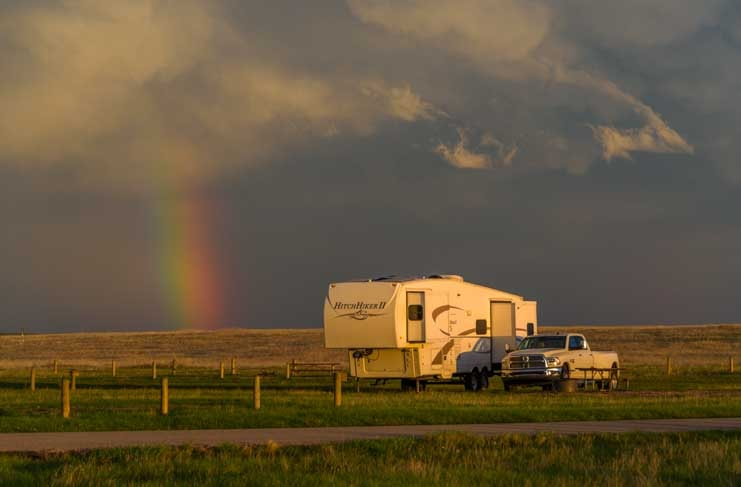 Fifth wheel trailer RV camping next to a rainbow-min