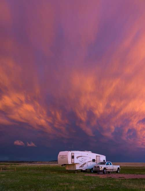 Pink sunset over fifth wheel trailer RV-min