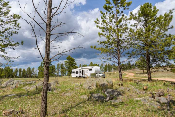 RV boondocking in the woods in a fifth wheel trailer-min