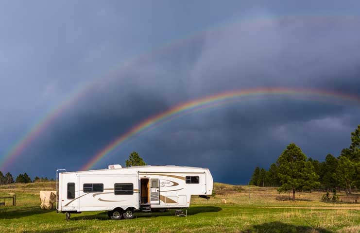 Double rainbow over fifth wheel RV trailer-min
