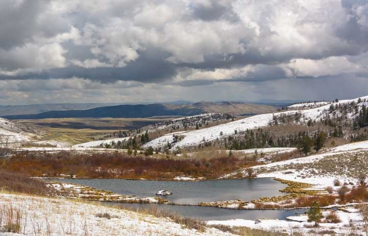 Ponds, clouds and snowy mountains in rural Wyoming RV trip-min