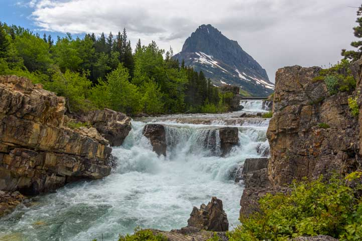 Thunderous waterfall Swiftcurrent Creek Many Glacier at Glacier National Park Montana-min