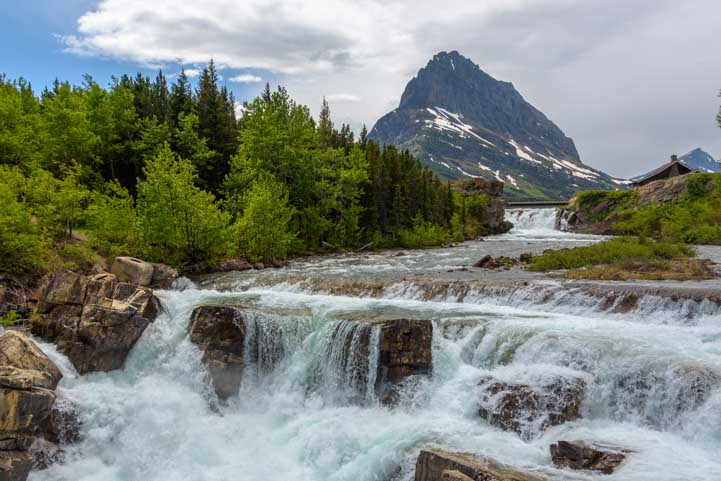 Huge waterfall Swiftcurrent Creek Many Glacier at Glacier National Park Montana-min