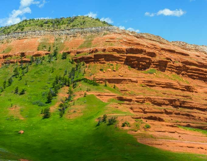 Green grass and red rocks Chief Joseph Highway Wyoming RV trip-min