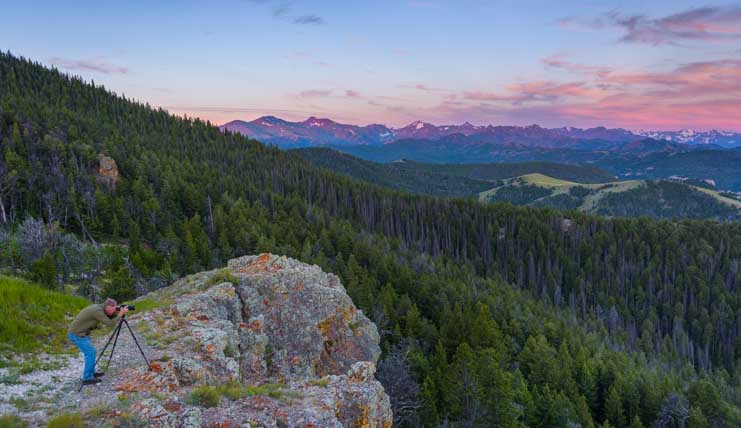 Photographer at sunrise Chief Joseph Scenic Highway Wyoming RV Trip Dead Indiand Summit-min