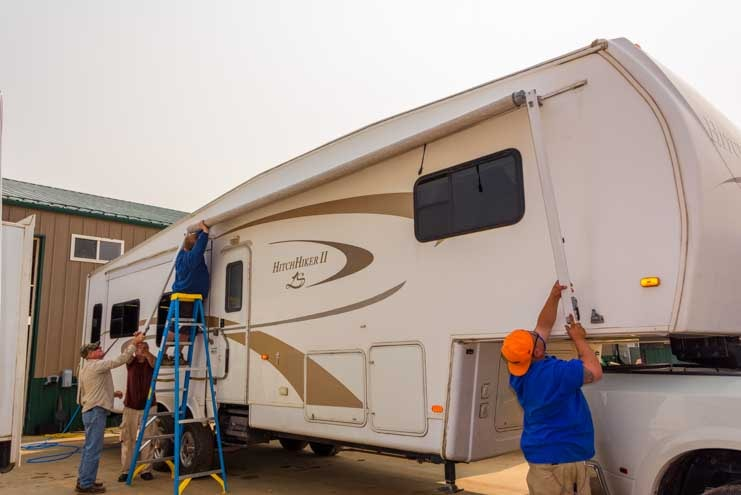 Slide the RV awning fabric along the track on the wall of the fifth wheel trailer RV-min