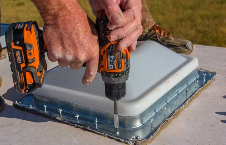 Use a cordless drill and #2 square bit to screw in new RV roof vent to fifth wheel trailer roof-min