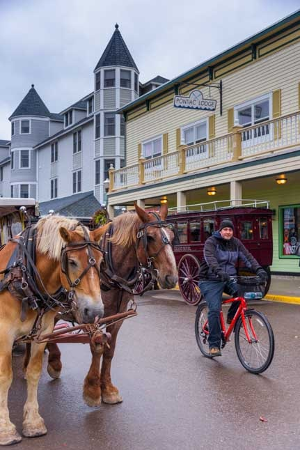 Horse drawn wagons and bicycles on Mackinac Island Michigan-min