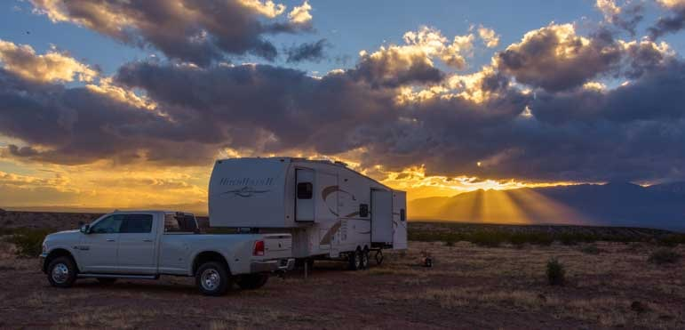 Sun breaking through clouds with fifth wheel RV-min