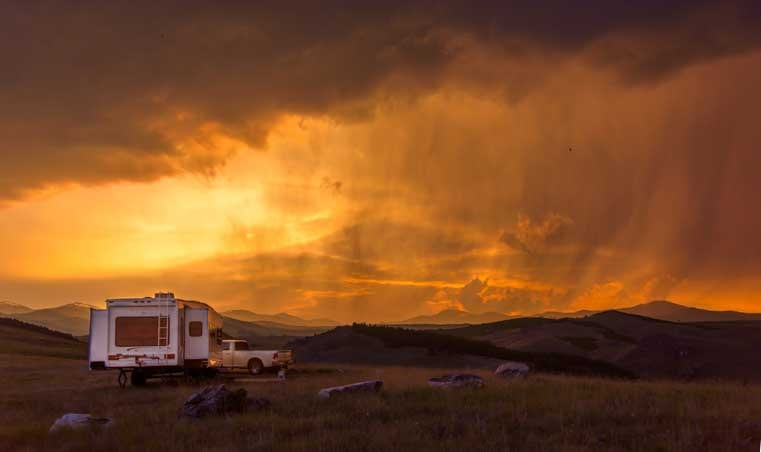RV camping in a fifth wheel trailer under stormy skies-min