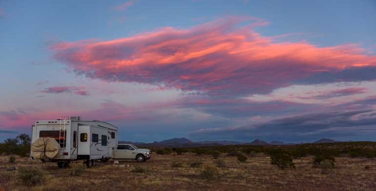 Pink cloud over an RV fifth wheel at sunset-min