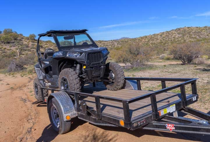 Polaris RZR 900 EPS XC UTV being loaded onto a utility trailer-min