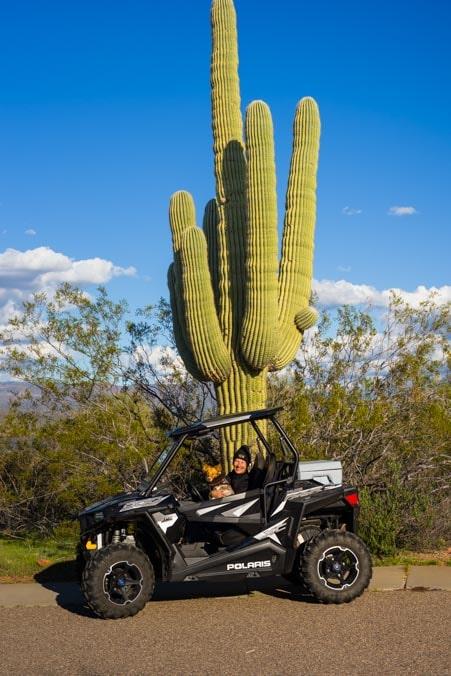 Happy campers in Polaris RZR next to saguaro cactus-min