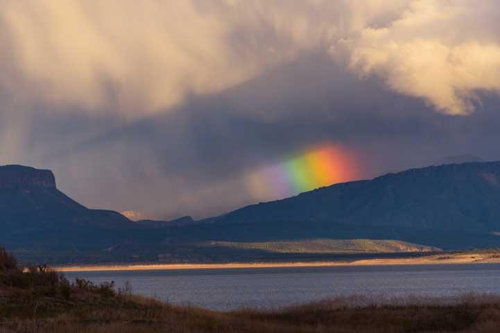 Rainbow behind cloud shadow on Roosevelt Lake-min
