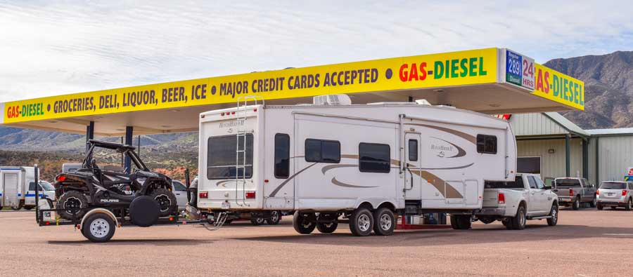 Gas station with RV dump station with triple tow Polaris RZR behind fifth wheel trailer-min