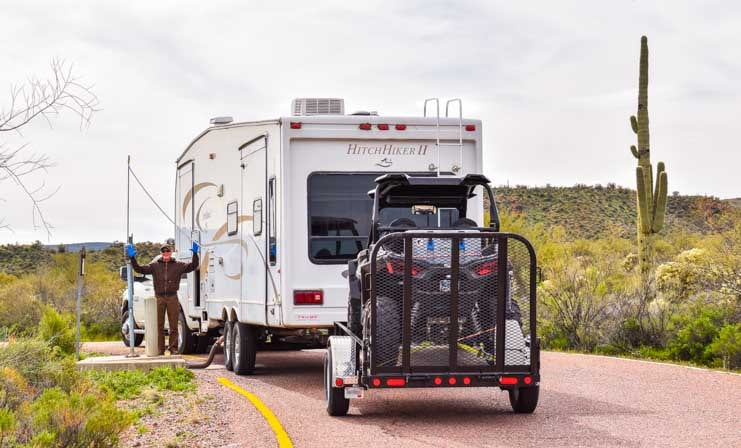 RV dump station with triple tow Polaris RZR behind fifth wheel trailer-min