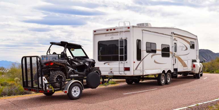 Triple tow Dodge Ram 3500 dually 36' fifth wheel and Polaris RZR on utility trailer-min