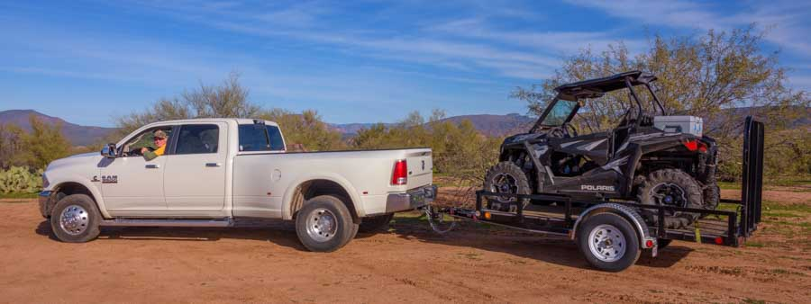 Ready to tow Polaris RZR 900 on utility trailer behind Dodge dually Ram truck-min