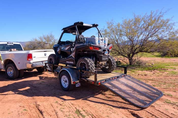 Preparing to tow Polaris RZR 900 XC EPS edition towed on utility trailer behind dually truck-min