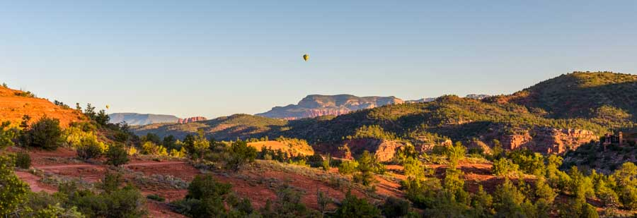 Balloons rise over red rocks in Sedona Arizona-min
