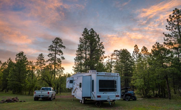 Fifth wheel RV in the forest at sunset-min