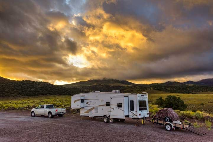 RV under stormy skies at sunset-min