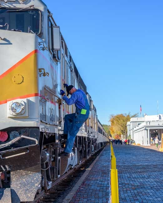Train engineer climbs out of Grand Canyon Railway train car-min