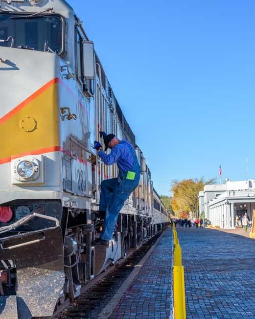 Train engineer climbs out of Grand Canyon Railway train car-min