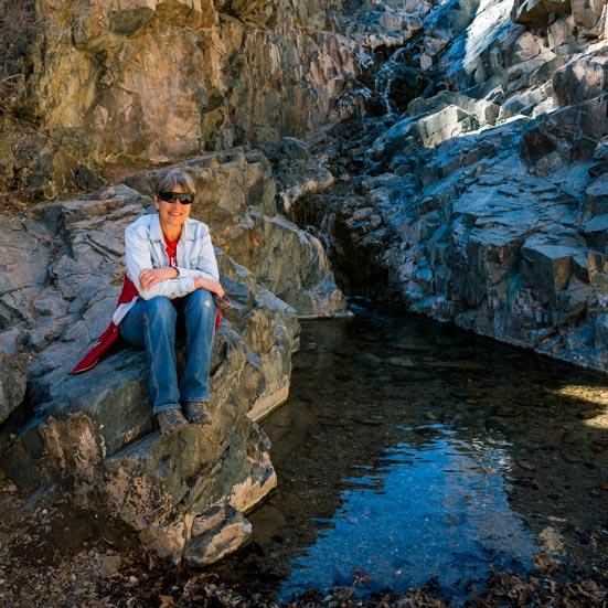 Happy camper sitting by a creek