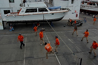 Workers play volleyball at Baja Naval