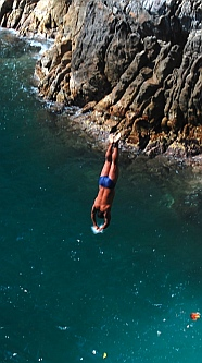 Cliff diver plunges into the water at La Quebrada.