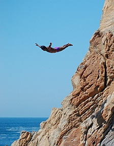 Cliff diver soars off the rocks at La Quebrada.